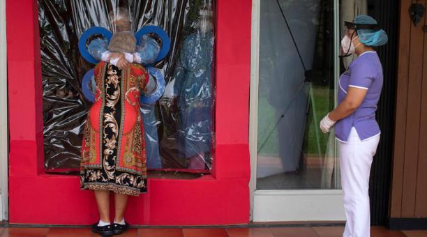 Una cortina permite abrazar a los ancianos en El Salvador