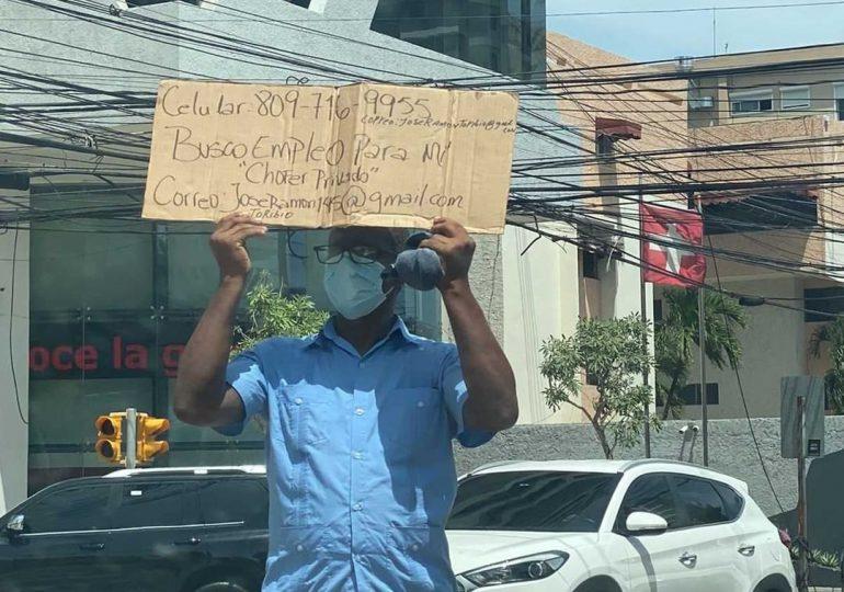 Hombre escribe en un cartón que solicita empleo como chófer privado