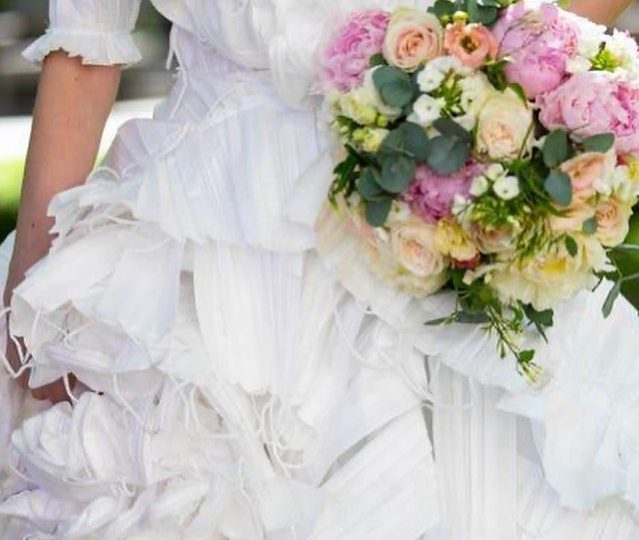 Modelo desfila vestido de novia diseñado con mascarillas